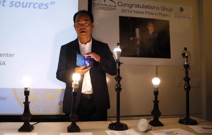 Scientist Shuji Nakamura holds an LED light after winning the 2014 Nobel Prize for Physics for inventing an energy-efficient