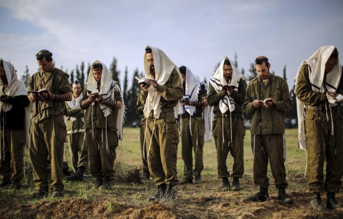 False: Israeli soldiers pray near the Gaza Strip. The author says Israel does not represent South African Jews and rejects the analogy between the Palestinian and apartheid struggles.
