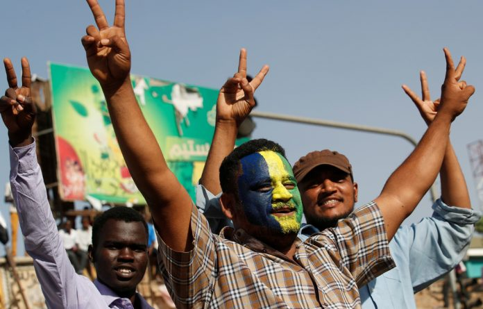 Sudanese protesters make victory signs outside the defence ministry compound in Khartoum