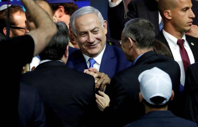 Israeli Prime Minister Benjamin Netanyahu is greeted by supporters of his Likud party as he arrives to speak following the announcement of exit polls in Israel's parliamentary election at the party headquarters.