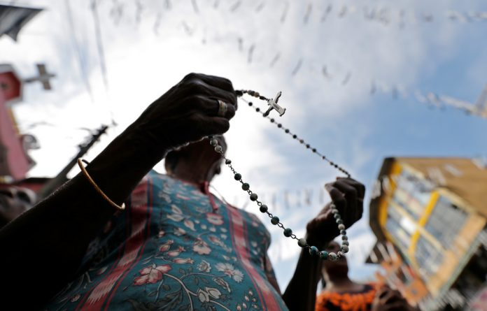 A woman holds a rosary as silence is observed as a tribute to victims