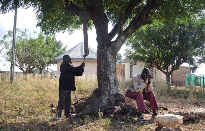 Clarion call: Khorombi Sadiki uses a piece of iron to beat a steel bar hanging from a branch