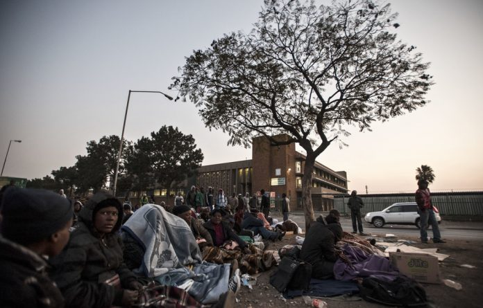 Invisible: Immigrants queue outside the home affairs department in Pretoria for permits and visas. South Africa is not living up to its constitutional obligation to meet the needs of all people.