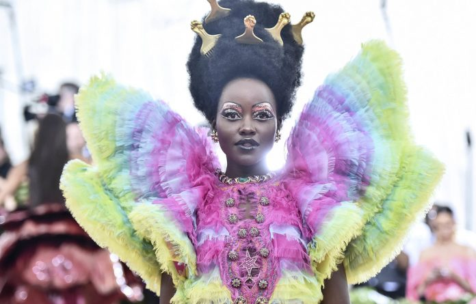 Rocking the rainbow: Actresses Lupita Nyong'o camped in an Afro with five gold Afro picks to match her rainbow-coloured shimmery organza gown.