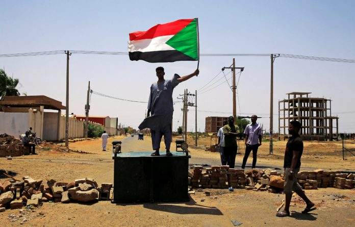 A Sudanese protester holds a national flag as he stands on a barricade along a street
