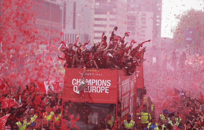Elation: Liverpool's squad atop a parade bus during their victory procession through the city of Liverpool with the UEFA Champions League trophy that they won by beating Tottenham Hotspur.