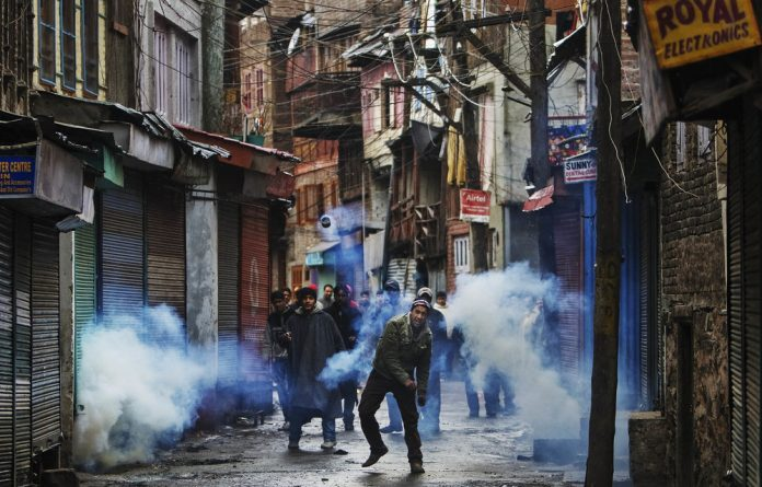 Outrage: A protester throws back a teargas canister shot by Indian police in Srinagar