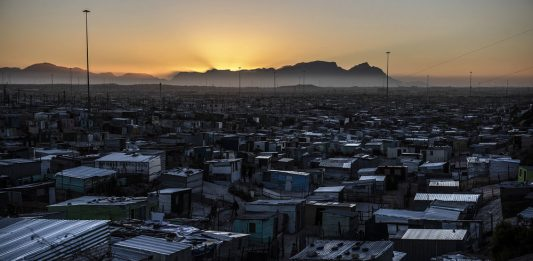 Nightfall: As the sun sets over Table Mountain the informal settlements become dark because homes have no electricity.