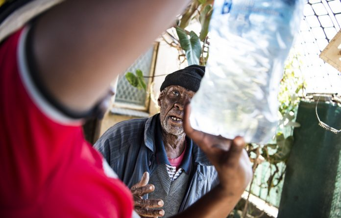 On the bottle: The 82-year-old James Mutle has to pay youngsters to chase after trucks that deliver drinking water otherwise he and others have to buy bottled water.