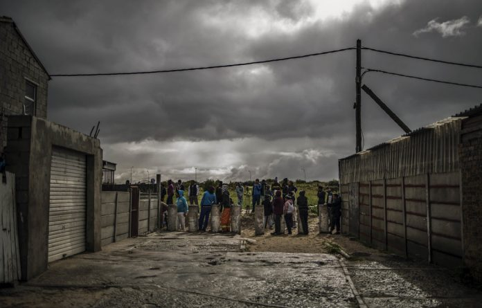 Protest nation: Residents gather to observe anti-riot policemen during a service delivery protest in the Cape Flats. Citizens are rejecting formal politics and elections in favour of the streets.