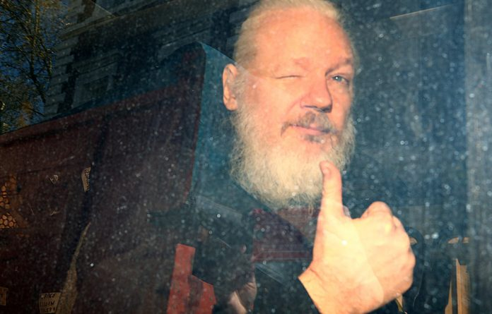 WikiLeaks founder Julian Assange makes a thumbs-up sign after police sensationally dragged him out of the Ecuadoran embassy in London in April 2019.