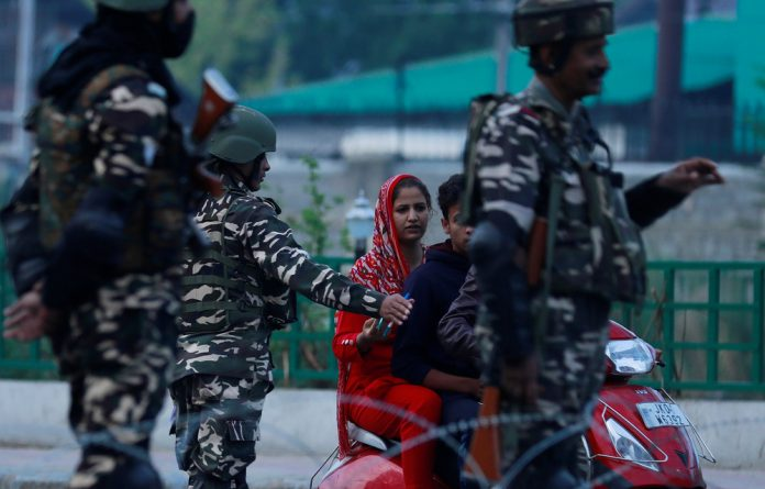 Indian security personnel stop Kashmiri residents as they stand guard on a deserted road during restrictions after scrapping of the special constitutional status for Kashmir by the Indian government