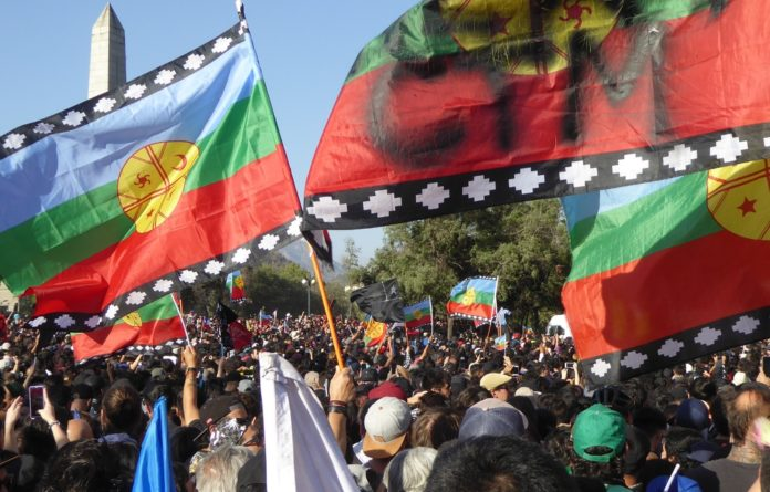 Symbol of resistance: Flags representing the indigenous Mapuche people of Chile are waved at a Inti-Illimani concert and demonstration in Plaza de la Dignidad in Santiago on December.