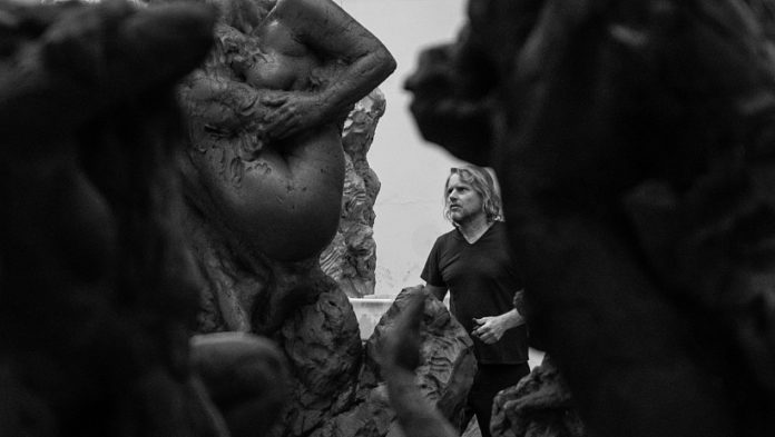 Sculptor Dylan Lewis stands among his statues