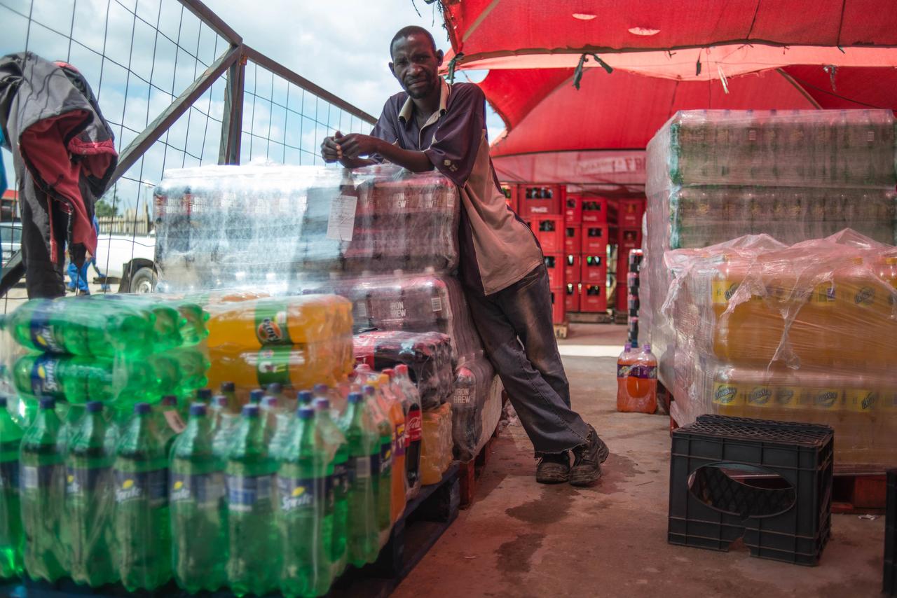 A man leans on a stack of sugar softdrinks (Mujahid Safodien/AFP)