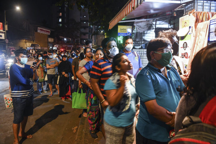 People in Mumbai line up outside a store to buy groceries