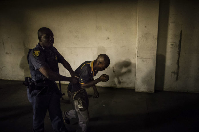 A resident of Jeppestown workers' hostel in Johannesburg is detained by a policeman during Operation Fiela in 2017. (Marco Longari/AFP/ Getty Images)