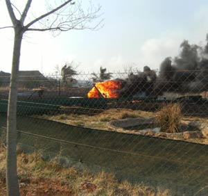 A structure in an animal enclosure burns on Sunday as a fire swept through the Rhino and Lion Nature Reserve in Gauteng